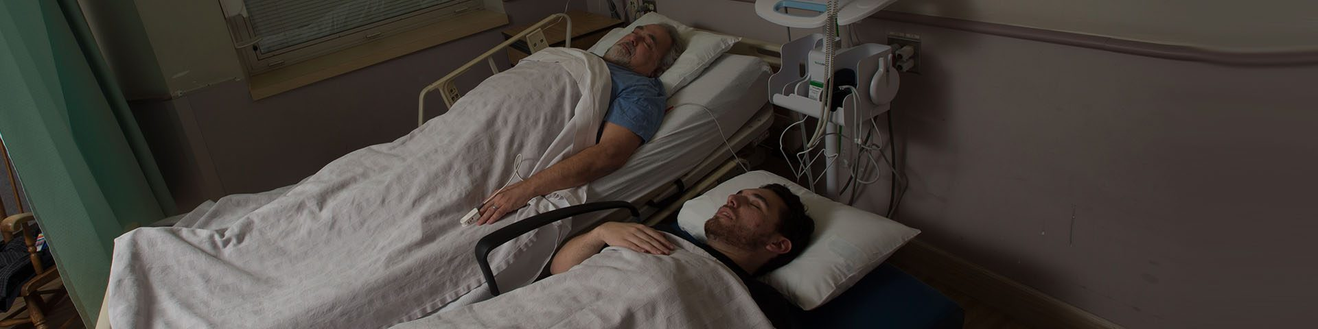 Father in hospital with son sleeping beside in sleeper chair