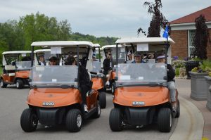 Golf carts and golfers getting ready to start golfing.